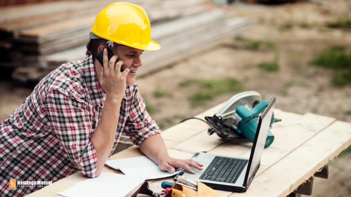 Construction contractor with phone and computer - in the office or the field, communication is key.