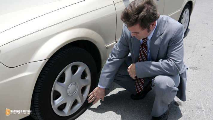 Businessman and vehicle with flat tire - time to call for emergency roadside assistance