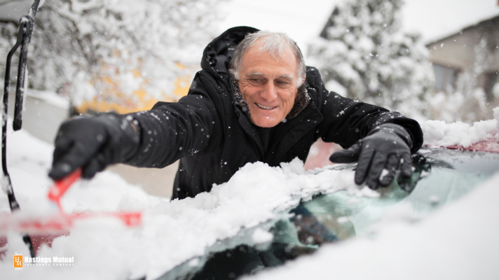 man cleaning snow off of car before winter driving